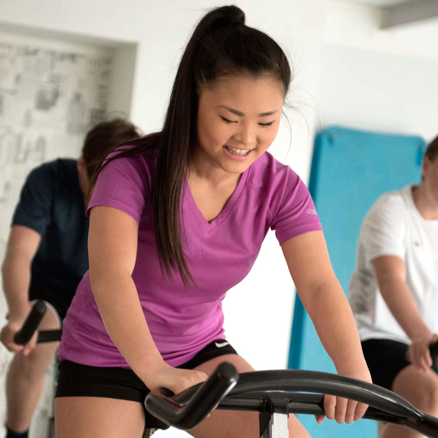 Jente trener på spinningsykkel